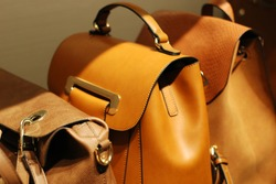 Several brown backpacks in the store on the shelf.