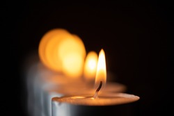 Several candles burning in a row. Photographed close-up.