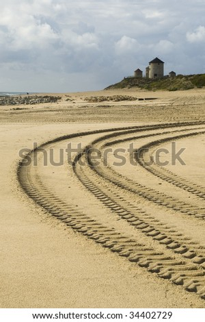 several car tracks in the sand with windmills on the background