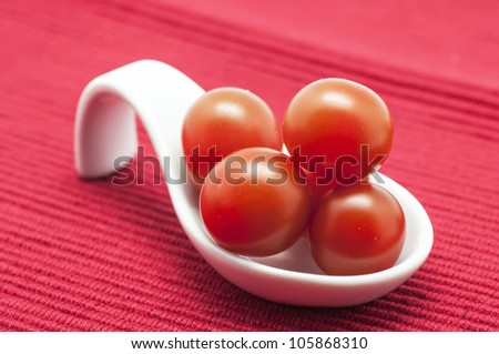 Several Cherry tomatoes on red tablecloth