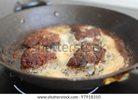 Several chops with roasted golden brown in boiling oil on old frying pan