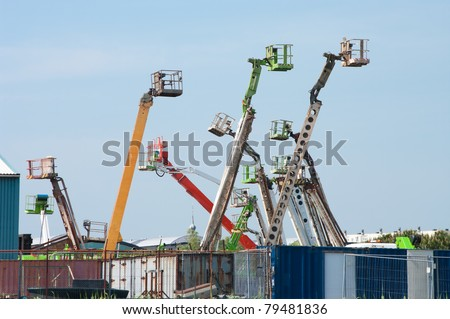 several colored boom lifts with cages