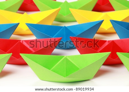 Several colored paper boats on white background