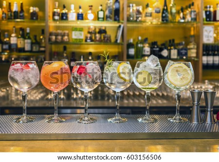 Several colorful cocktails in large wine glasses in a row in a classic bar environment with dozens of blurry liquor bottles in the background. #603156506