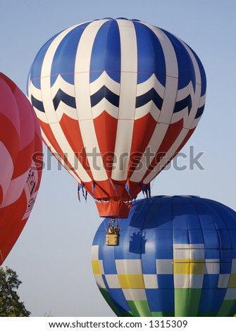 Several colorful hot air balloons launch into a bright blue sky
