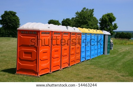 Several colorful outdoor toilets lined up ready for an outdoor event.
