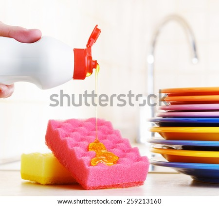 Several colorful plates, a kitchen sponges and a plastic bottle with natural dishwashing liquid soap in use for hand dishwashing. Eco-friendly, toxin-free, green cleaning product. Dishwashing concept.