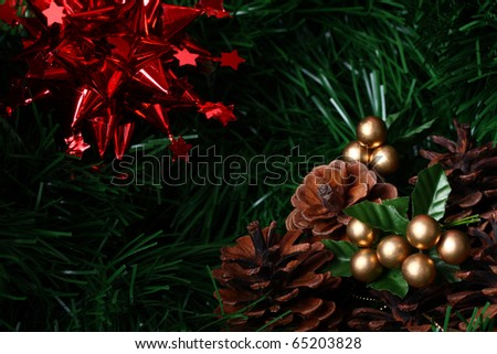 Several cones placed on green fir with red decoration star and copy space