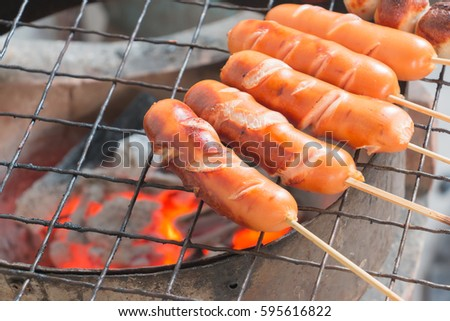 Several cooking hot dogs on a grill #595616822