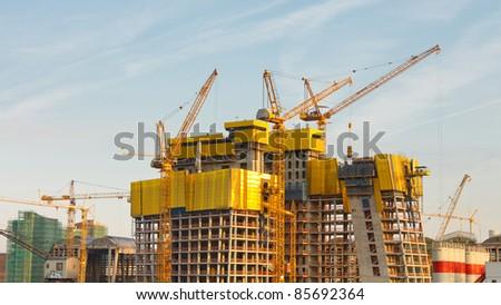 Several cranes at a concrete high-rise construction site