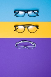 several different glasses on a colorful background, top view,  a store of glasses, adult and children's glasses