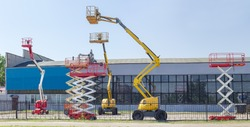 Several different wheeled scissor lifts and wheeled articulated lifts with telescoping boom and basket on an asphalt ground against the sky and an industrial building