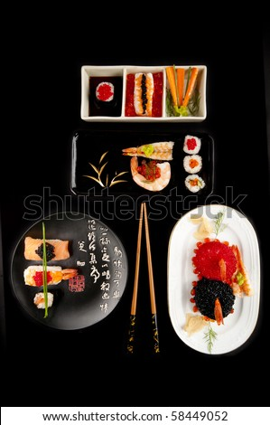 Several elegant sushi dishes with norimaki and nigiri sushi, a variety of colourful fish eggs a selection of plates and chopsticks. On black.