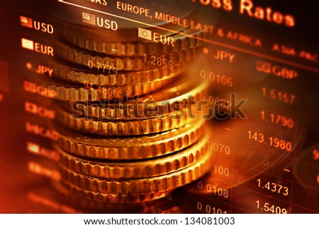 Several euro coins and finance data. Selective focus.