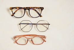 several fashionable stylish glasses on a beige background place copy top view, optics store concept