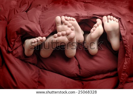 Several feet poking out of blankets on bed