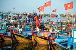 several Fishing boats with red flags in marina at Nha Trang, Vietnam