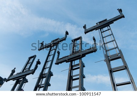 several forklifts for containers against a blue sky