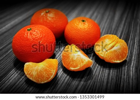 Several fresh ripe tangerines and peeled tangerine slices on wooden surface. Closeup. Selective focus.   #1353301499