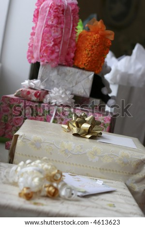 Several gift-wrappped wedding gifts of various sizes next to each other