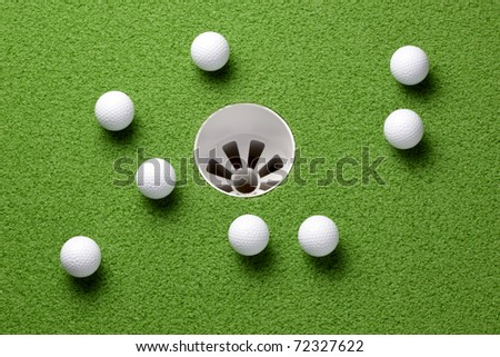 Several golf balls near hole on putting green