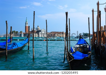 Several Gondola moored with the Maggiore church in the background in the Italian city of Venice
