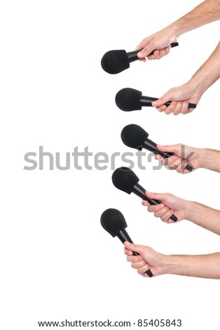 Several hands holding microphones