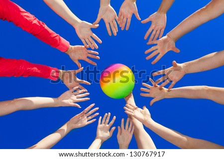 Several hands reaching out together in a circle for volley ball against blue sky