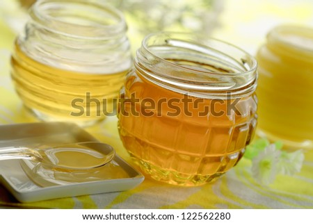 Several honey jars  and a honey  dripping from spoon
