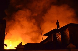 Several houses caught fire, man standing on the roof of the house. Feel so sad and panic see the fire gets bigger burning their house.