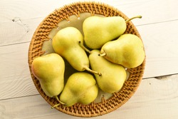 Several juicy ripe, light yellow pears with a ceramic plate, on a wooden table, close-up, top view.
