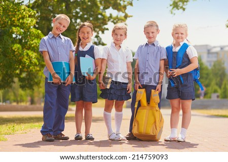 Several kids in school uniform outside