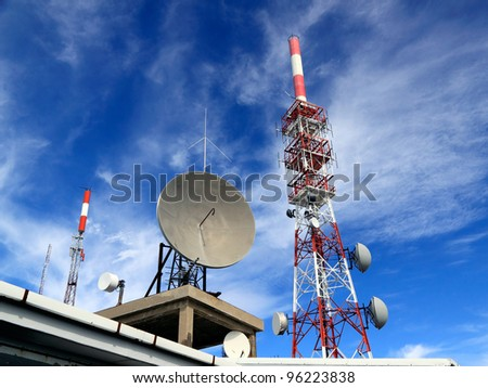 Several kind of communication antennas and a red and white tower
