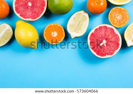 Several kinds of whole and cut citrus on a blue background - Shutterstock ID 573604066