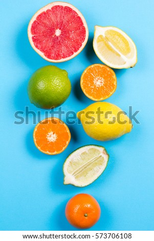 Several kinds of whole and cut citrus on a blue background - Shutterstock ID 573706108