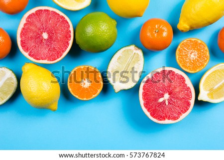 Several kinds of whole and cut citrus on a blue background - Shutterstock ID 573767824
