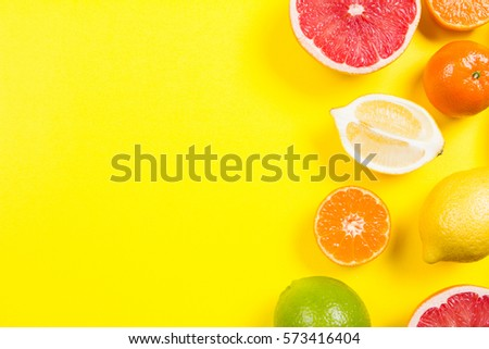 Several kinds of whole and cut citrus on a yellow background - Shutterstock ID 573416404