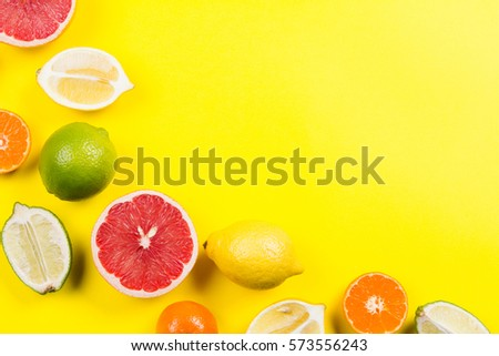Several kinds of whole and cut citrus on a yellow background #573556243