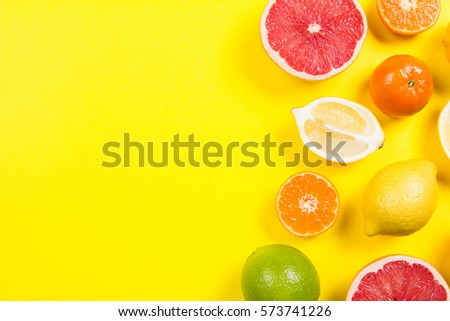 Several kinds of whole and cut citrus on a yellow background - Shutterstock ID 573741226