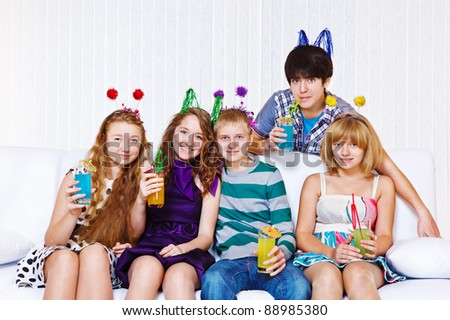 Several laughing young people having cocktail party
