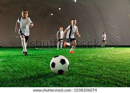 Several little football players running sfter soccer ball down green field #1038206074