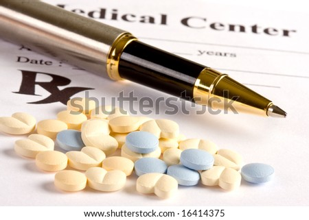 Several little pills and a pen lying on a prescription document