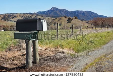Several mailboxes place in a rural area with hillside behind them.