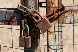 several metal rusted locks with a chain, which closed the metal cage, closeup