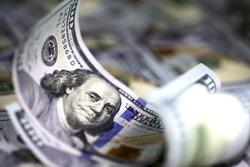 Several modern hundred us dollar bills, curved upward, lying on the background of hundred us dollar banknotes. Close up image. Selective light. Selective focus.
