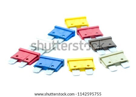 Several multi-colored car fuses for the fuse box are laid out in a triangle. Replacing the electric fuses in the car. Isolate on white background. The second plan of the photo is blurred.