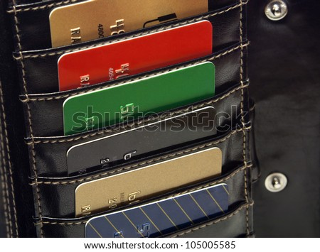 Several Multicolored  red green black  blue gold credit cards in the black wallet.