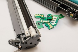 several, multiple, a set of different chips, microchips lies on the table near the disassembled cartridge from the laser printer