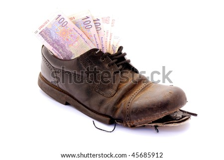 Several one hundred South African Rand notes in a black old broken leather shoe of a hobo. Image isolated on white studio background.