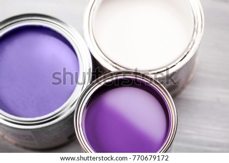 Several opened cans with paint inside. Ultra Violet and white colors of paint. Close up.
